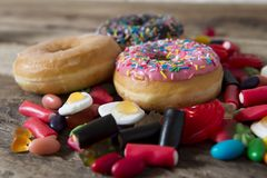 Unhealthy but delicious group of sweet sugar donut cakes and lots of gummy candies on vintage wooden table royalty free stock photography