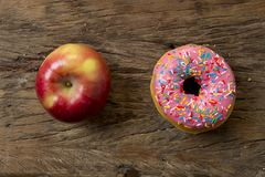 Unhealthy but delicious sweet sugar donut cake versus healthy apple fruit on vintage wooden table in lifestyle nutrition Royalty Free Stock Image