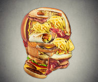 Unhealthy diet health concept fast food in shape of human head Stock Photos