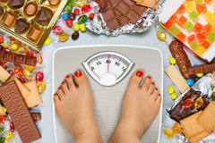 Unhealthy diet - overweight. Feet on bathroom scale and chocolate, jelly cubes, candies, chocolate bars, cookies, donuts royalty free stock image