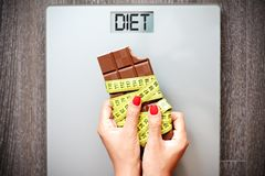 Unhealthy diet concept with woman hand holding chocolate bar on weighting scale with rolled measurement tape. Unhealthy diet with woman hand holding chocolate royalty free stock images