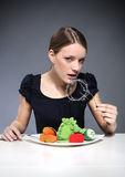 Unhealthy diet. Young girl sitting over a plate of vegetables and put into the mouth barbed wire stock photos