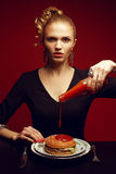 Unhealthy eating. Junk food concept. Girl eating burger. Unhealthy eating. Junk food concept. Portrait of fashionable young woman holding bottle with tomato royalty free stock photography