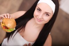 Unhealthy eating. Junk food concept. Portrait of fashionable young woman holding burger and posing over wood background. Close up. Copy-space. Perfect hair royalty free stock images