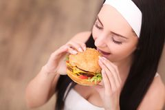 Unhealthy eating. Junk food concept. Portrait of fashionable young woman holding burger and posing over wood background. Close up. Copy-space. Perfect hair stock images