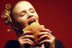 Unhealthy eating. Junk food concept. Guilty pleasure. Portrait of happy fashionable model holding burger & eating over red background. Perfect hair, skin, make stock photo