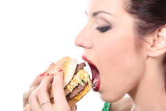 Unhealthy food. Close-up portrait of young beautiful woman is eating big mac isolated on white Stock Photos