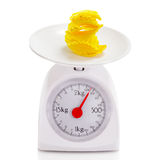 Unhealthy food on balance scale Stock Images