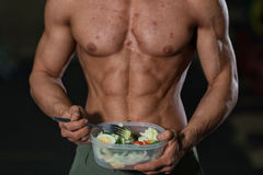 Unhealthy food concept, athlete body with pimples. Unhealthy food concept, male athlete body with pimples. Bad diet, muscular man with vegetables stock photography