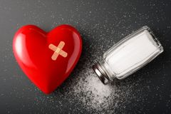 Unhealthy food concept - salt. Heart and salt shaker on dark background stock photography