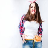 Unhealthy food fat woman concept, Hungry girl XXL bad food, Mode. L plus size hold burgers centimeter female well-fed with fatty stomach in shirt web design royalty free stock image