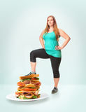 Unhealthy food and fat woman. A fat woman steps on the burger. Unhealthy food. The concept of dieting and healthy lifestyle for fat woman royalty free stock photo