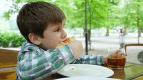 Unhealthy food, little boy drinks apple juice from a glass and eats a slice of pizza in cafe in open air. Unhealthy food, little boy drinks apple juice from a stock video footage
