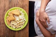 Fried Food In Front Of Person Having Stomach Pain. Unhealthy Food On Plate In Front Of Person Having Stomach Pain royalty free stock image