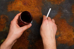 Unhealthy habits concept. Man holding cigarette and glass of red wine in his hands. Bad unhealthy habits or new year resolution concept. Copy space Stock Photo