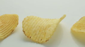 Unhealthy Harmful food, yellow delicious Potato ribbed crispy chips Lie in a row on a white table background, close-up footage mov stock video