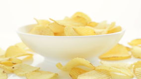 Unhealthy Harmful food, yellow delicious Potato ribbed crispy chips randomly lying in bowl and on a white table background, close- stock video