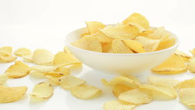Unhealthy Harmful food, yellow delicious Potato ribbed crispy chips randomly lying in bowl and on a white table background, close- stock video footage