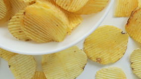 Unhealthy Harmful food, yellow delicious Potato ribbed crispy chips randomly lying in bowl and on a white table background, close- stock footage