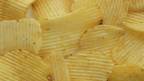 Unhealthy Harmful food, yellow delicious Potato ribbed crispy chips randomly lying on a white table background, close-up footage m stock video footage