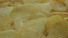 Unhealthy Harmful food, yellow delicious Potato ribbed crispy chips randomly lying on a white table background, close-up footage m stock footage