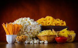 Unhealthy Junk Food. Different Types of Junk food, Popcorn, salty-sticks, salty-crackers on wooden table in still-life Stock Images