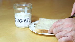 Unhealthy junk food, sugar. A hand with a spoon putting pure sugar onto a piece of bread to eat. Junk food stock video footage