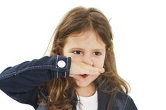 Unhealthy little girl in jeans jacket, closed his nose with his hand, the girl sneezes from allergies. Close-up.Isolated on white background Stock Photo