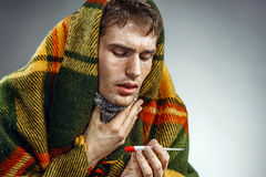 Unhealthy man suffering from sore throat. Photo of sick man wrapped in blanket with thermometer Stock Images