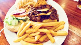 Unhealthy meal with mexican nacho chips loaded with beef, cheese, fries, onion rings Stock Photo