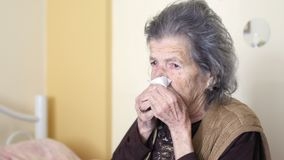 Unhealthy old woman get flu cold, blowing nose stock video