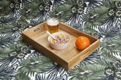 Unhealthy quirky breakfast with beer. A quirky wooden tray serving a unhealthy breakfast on an exotic print of leaves background. Minimal still life color stock photos