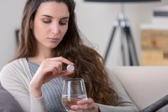 Unhealthy sick woman takes pill with glass of water Stock Photos