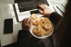 Free Unhealthy Snack At Work Time, Woman Overeating Stock Photos - 215784923