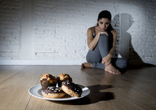 Unhealthy sugar donuts and muffins and tempted young woman or te Royalty Free Stock Image