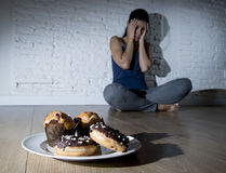 Unhealthy sugar donuts and muffins and tempted young woman or te. Enager girl sitting on ground worried about overweight in diet and weight loss obsession in Stock Images