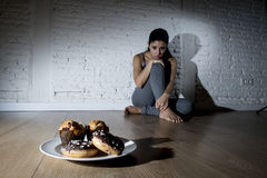 Unhealthy sugar donuts and muffins and tempted young woman or teenager girl sitting on ground. Worried about overweight in diet and weight loss obsession in Stock Image