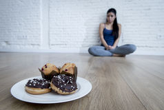 Unhealthy sugar donuts and muffins and tempted young woman or teenager girl sitting on ground Stock Photography