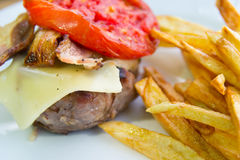 Unhealthy but tasty. Meat with bacon, tomato and french fries Stock Photography