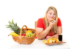 Unhealthy woman eating junk food rather than fruit Stock Photos