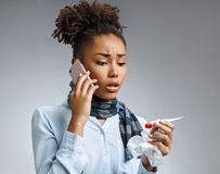 Unhealthy woman with high temperature calling on the phone. Photo of african american woman in blue shirt suffering cold and winter flu virus on gray stock image
