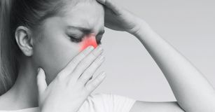 Unhealthy woman in pain touching her head and nose stock images