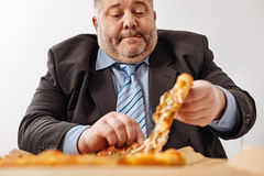Unhealthy worker having some junk food for lunch Royalty Free Stock Images