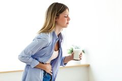 Unhealthy young woman with stomachache holding a glass with milk at home. Shot of unhealthy young woman with stomachache holding a glass with milk at home stock photo