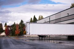 Dry van semi trailer loading and unloading in warehouse dock gat. Unhooked long dry van semi trailers stand e by e for loading and unloading in warehouse dock Royalty Free Stock Photos