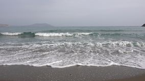 Unhurried waves of the Black sea run on the sandy shore. Calm cloudy day. Fog stock video