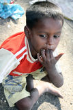 Unhygenic Poor Boy. A portrait of a unhygenic poor kid from India, sucking on his dirty fingers Royalty Free Stock Photo