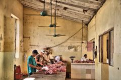 Unhygienic meat shop. SANCTI SPIRITUS, CUBA - FEBRUARY 7, 2011: Men work in an unsanitary meat shop in Sancti Spiritus. Cuba`s retail industry struggles to Royalty Free Stock Image