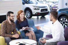 União feliz que compra o carro novo ao falar com vendedor em um dea fotografia de stock