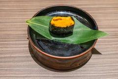 Uni japansk mat för sushi i svart platta på trätabellen Fotografering för Bildbyråer